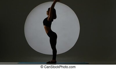 Gymnast performs a forward and backward tilt. Back light. Silhouette