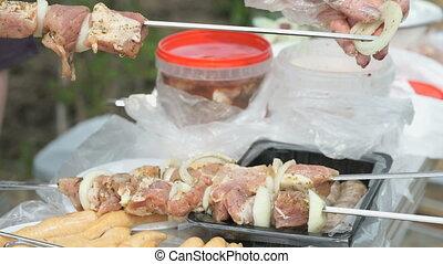 Woman's hand prepares raw meat for cooking kebabs - Skewered...