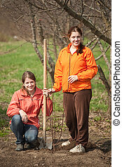 women making orchard - Two young women making orchard with...