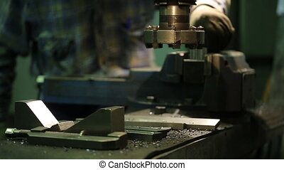 Factory worker sets metal piece in vise of a milling...