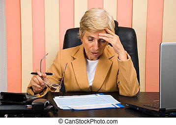 Worried elderly woman working in office