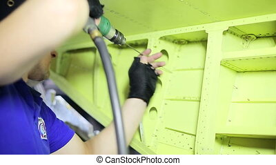 Worker drills holes in fuselage of aircraft long drill....
