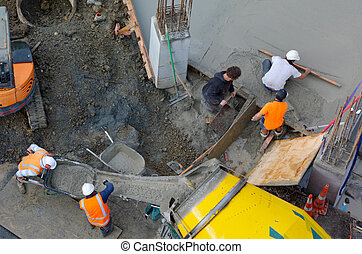 Construction site workers leveling cement in building site -...