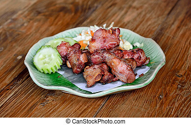 Fried sparerib on the wooden background .