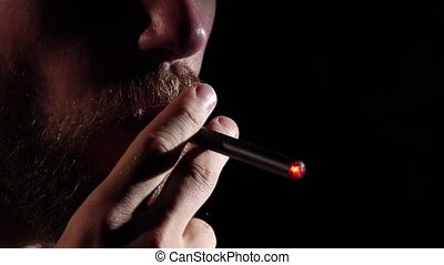 Man with a beard smoking electronic cigarette. Black. Close...