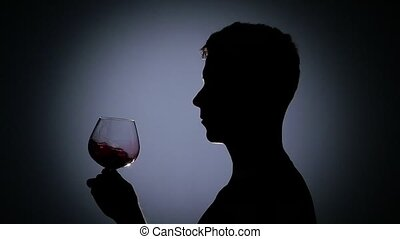 Man is drinking cognac. Black. Back light. Silhouette. Slow motion