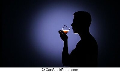 Man drinking whiskey. Blue back light