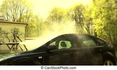 Man washing the windscreen of his car in a cubicle with high...