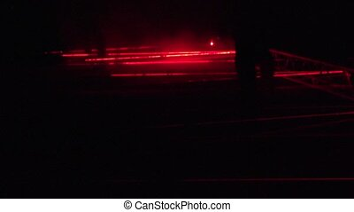 People climb over red protective laser in light design...
