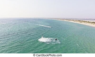 Man flying over sea on flyboard. Aerial view from copter....
