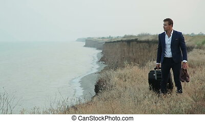 Business man with a travel bag near a cliff by the sea.