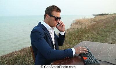 Businessman checking his diary against beach scene. Series.