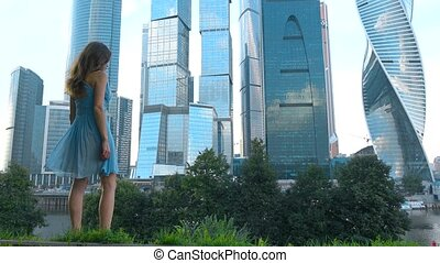 Slender girl in blue dress looking at modern skyscrapers of Moscow city, Russia, 4K footage
