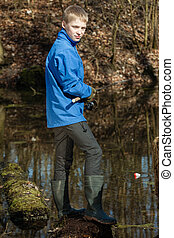 Handsome teen fisherman at pond with rod - Single blond...
