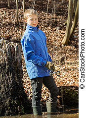 Boy in shallow pond fishing with rod - Single smiling...