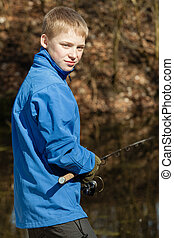 Grinning teen fisherman at pond with rod - Grinning single...