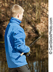 View from behind of boy with fishing rod
