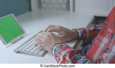 Male hands a plaid shirt typing on wireless keyboard with...