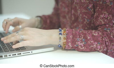 Beautiful female hands with rings printed on laptop She has...