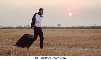 A man in a business suit comes with a travel bag on a field of harvested wheat.