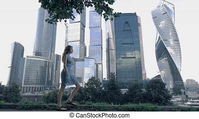 Skinny girl in blue dress walking against modern glassy skyscrapers. Bleached colors. Super slow motion shot, 250 fps