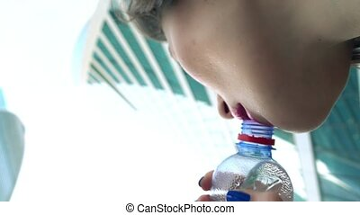 Young girl drinking water from small bottle against...
