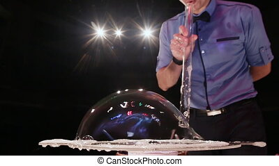 The man the actor blows big a soap bubble on a table. Soap bubbles show.