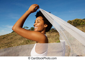 Beautiful young woman holding white fabric at wind on a...