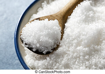 Sea Salt Flakes - Bowl of sea salt flakes, with small wooden...