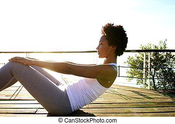 Healthy young woman doing abs crunches - Side portrait of...
