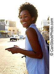 Cheerful african american woman with cell phone outdoors