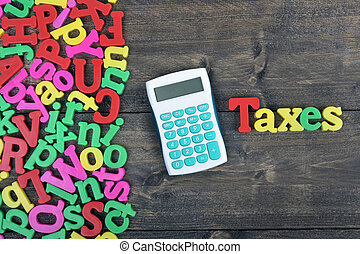 Taxes on wooden table - Taxes word on wooden table