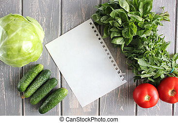 Paper leaf and composition of vegetables on grey wooden...