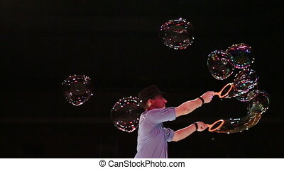 The man the actor sprays big soap bubbles by means of forms....