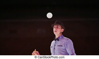 The man the actor blows three soap bubbles with a gray smoke and plays with them in tennis. Soap bubbles show.