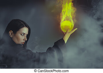 Magician woman with a fire ball in her hands