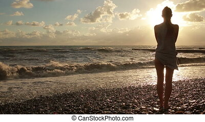 girl undresses at the sea silhouette of a beautiful woman He...
