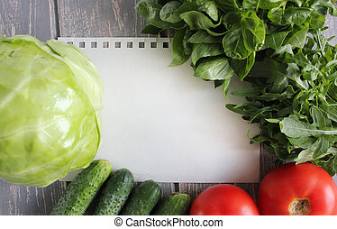Paper leaf and composition of vegetables on grey wooden desk...