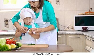Mom teaches child to clean cucumber