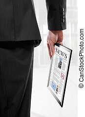 Businessman holding a touchpad pc with a newspaper