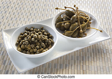 Capers and Caper Berries - Small white bowls of capers and...