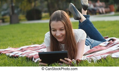 Girl with Touchscreen Tablet Lying on Grass in Sunny Lights