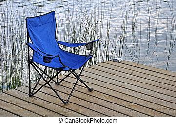 Blue beach chair on dock - Blue empty beach chair on dock on...