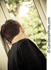 Rear View of Teenage Boy Looking Out Window - Head and...