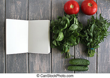 Note book and composition of vegetables on grey wooden desk...