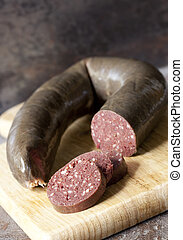 Black Pudding - Black pudding, with cut slices, on chopping...