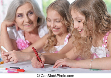 Old woman with tweenie girls drawing at home