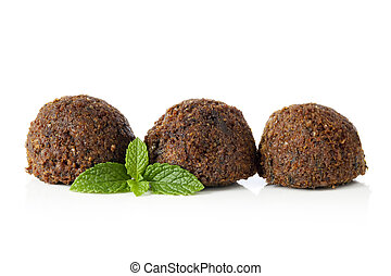 Falafel balls, isolated on white with a sprig of mint.