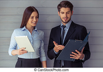 Beautiful business couple with gadget - Beautiful young...