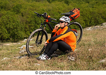 Active man sitting on bike and eating sandwich. Healthy...